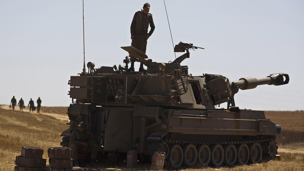 An Israeli soldier stands atop a mobile artillery unit stationed near the border with the Gaza Strip